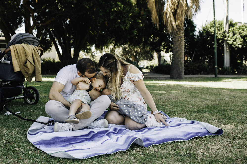 family-of-four-sitting-on-picnic-rug.jpg