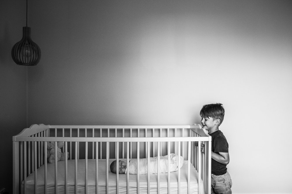 little-boy-leaning-over-sisters-crib (1 of 1).jpg
