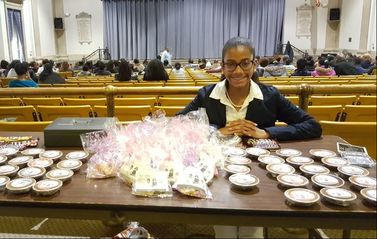 A professional young woman sits next to her merchandise