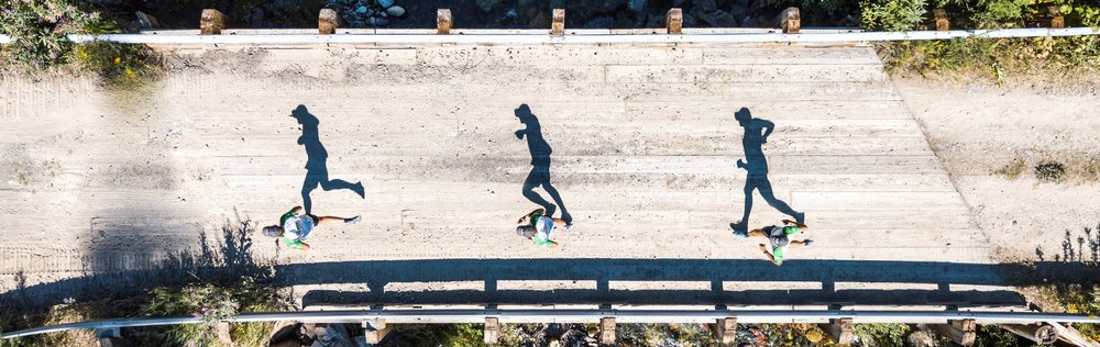 runners shadows crossing a bridge in Montana
