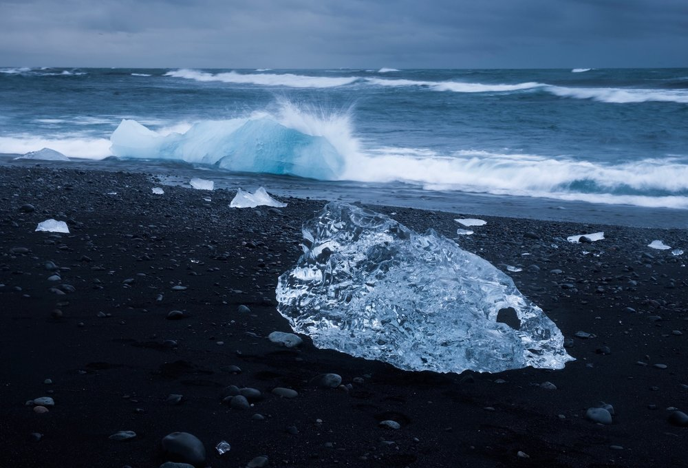 Black volcanic sand and chunks of iceberg hit by the ocean