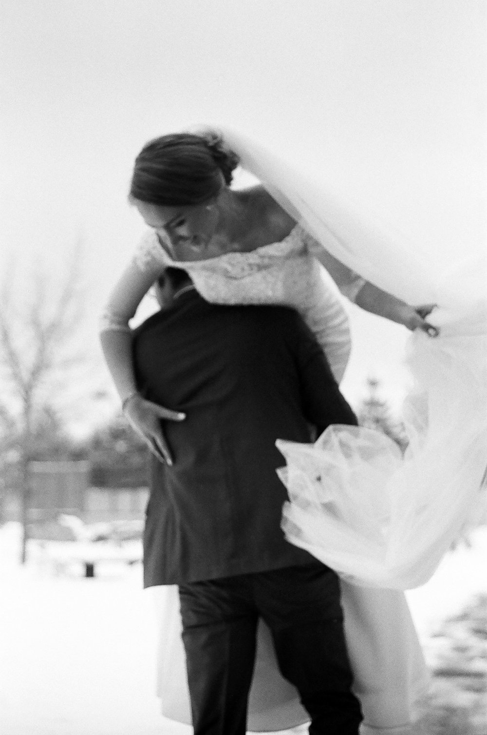Black-and-white photograph Groom carrying his bride on their wedding day inSnowy Mountains of Albuquerque New Mexico
