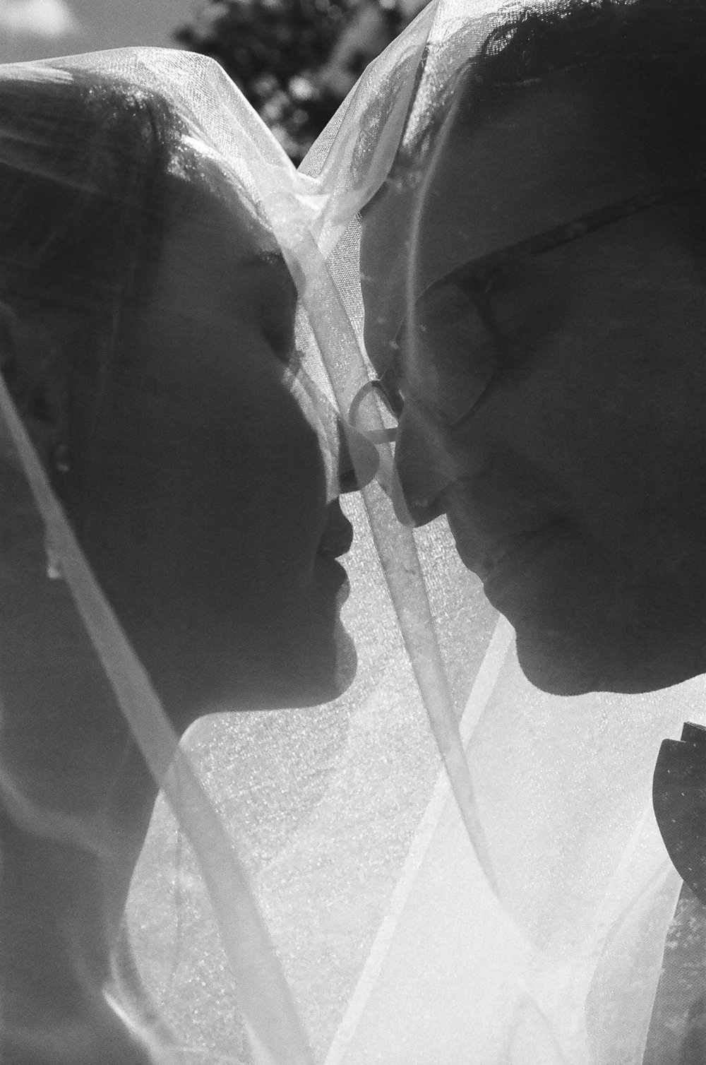 black and white 35mm film photograph of bride and groom Kissing under the veil taken by Joseph Barber wedding photography newport beach