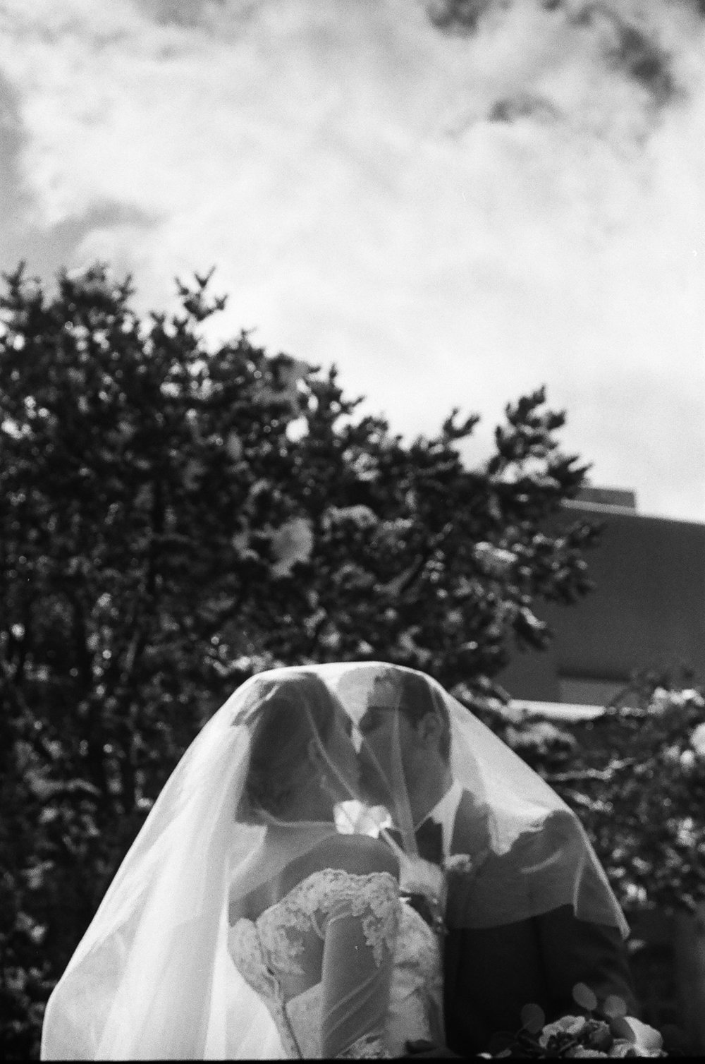 Black-and-white photograph of bride embracing Her groom on their wedding day inSnowy Mountains of Albuquerque New Mexico