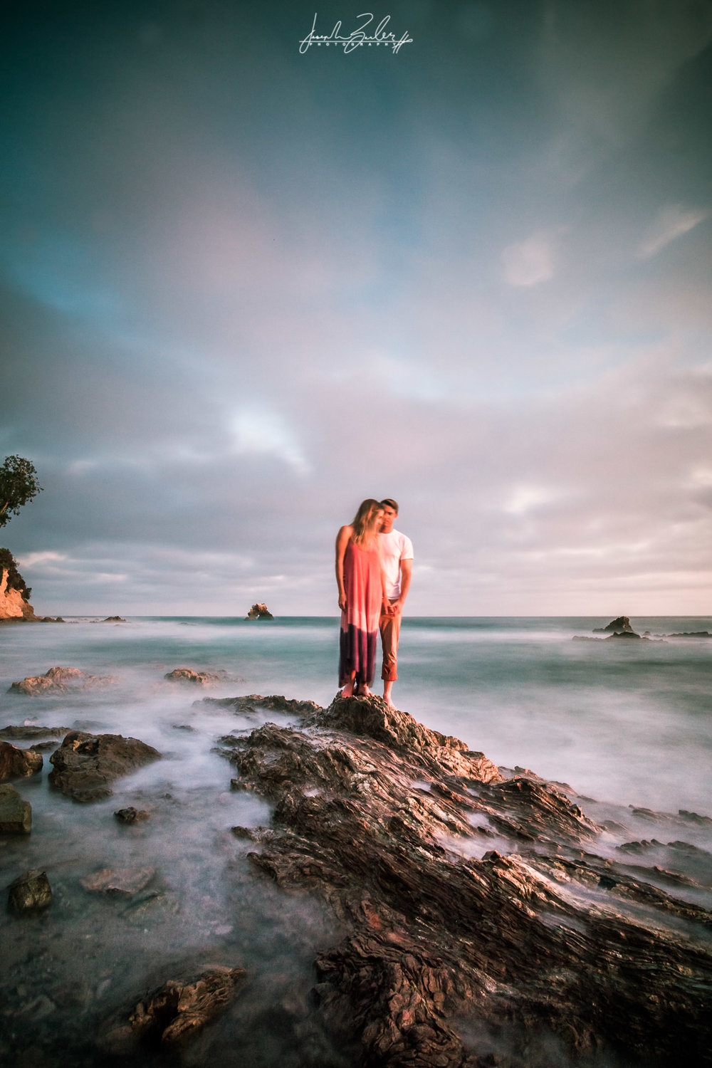Long exposure photograph of a couple standing on tide pool rocks With Misty Waves and clouds at golden hour at Little Corona Beach during their engagement session