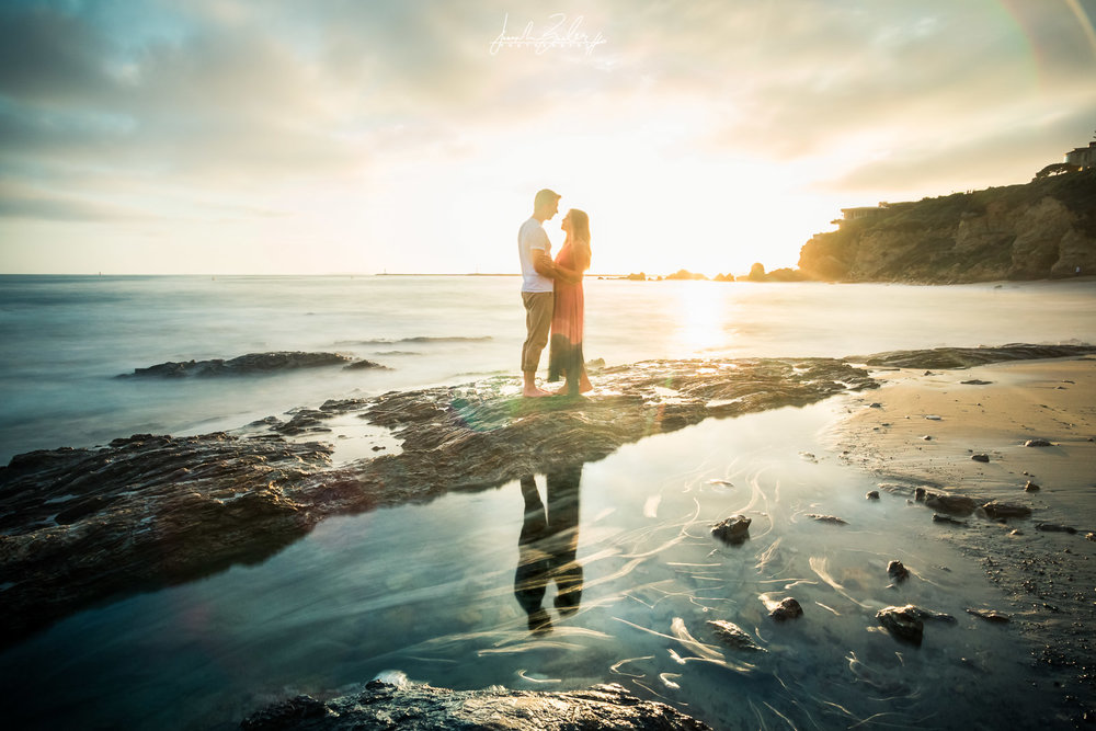 Long exposure photograph of a couple standing on tide pool rocks With glassy reflection at golden hour at Little Corona Beach during their engagement session
