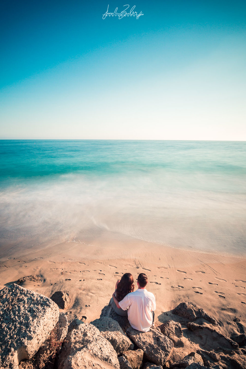 Long exposure photograph of a couple Sitting on the rocks at Crystal Cove State Beach with a Misty ocean at golden hour at during their engagement session