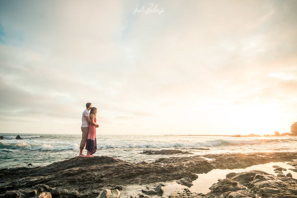 Engagement session photograph of a couple holding each other on top tide rocks during  during Golden hour at little corona del mar beach