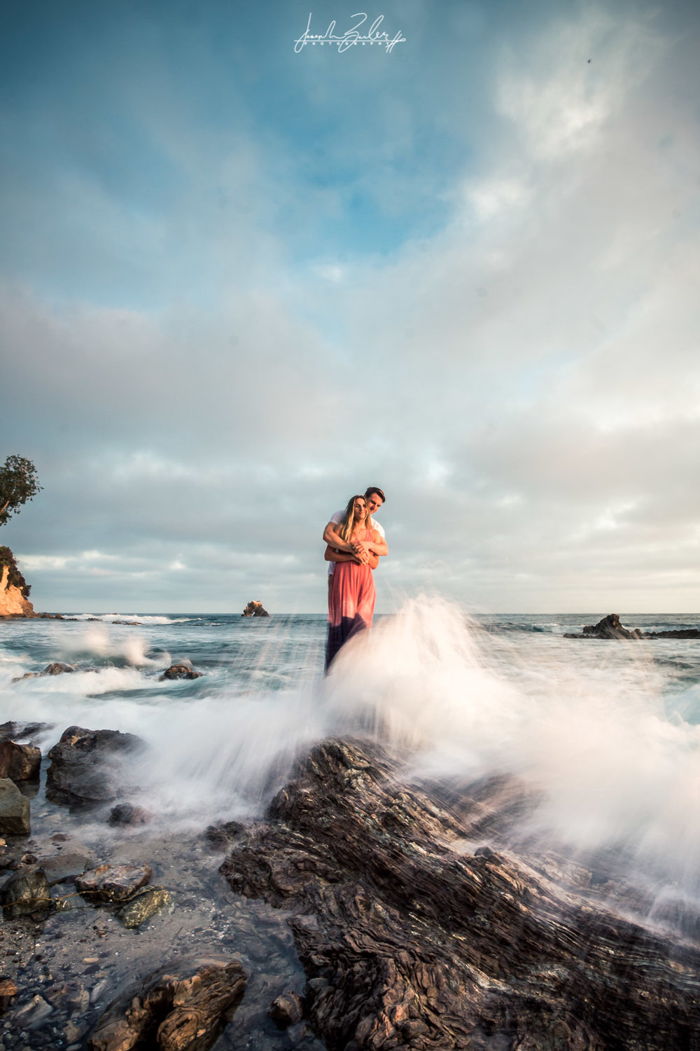 Engagement session photograph of a couple holding each other on top tide rocks With breaking waves during  during Golden hour at little corona del mar beach