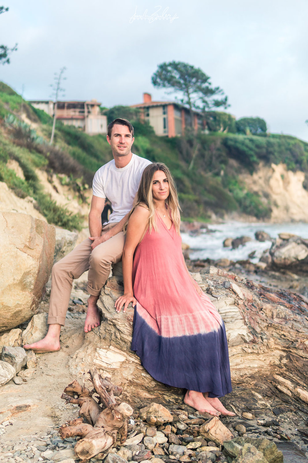Engagement session photograph of a Couple posing On a rock during  during Golden hour at little corona del mar beach