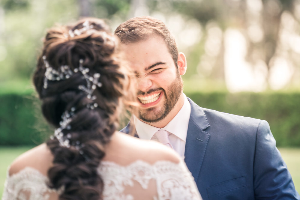 Portrait of the groom turning and smiling  to see his bride during the first book on their wedding day in Brea California