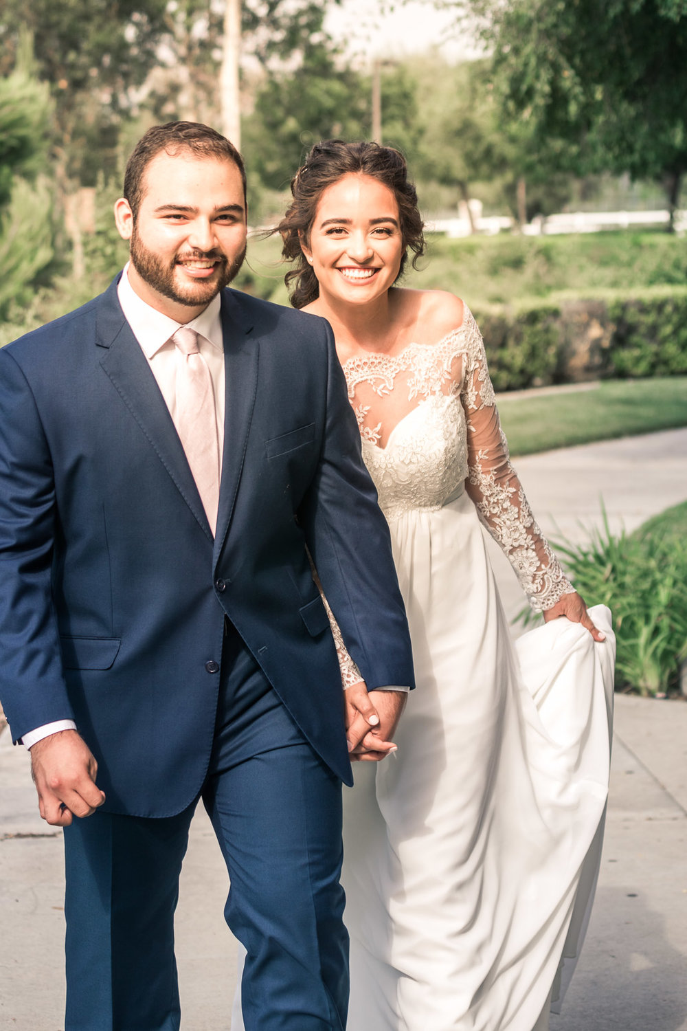 Portrait of the Bride and Holding hands and smiling   during the first book on their wedding day in Brea California