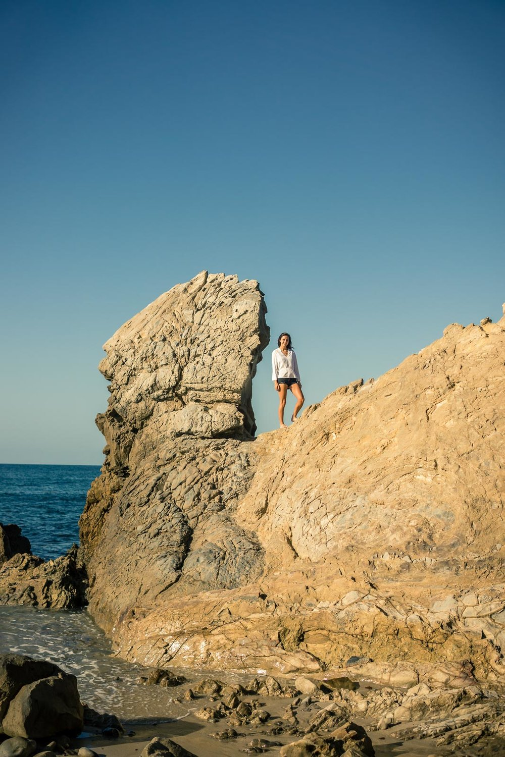 Graduation portrait of a female student posing on the rocks Corona Del mar state beach