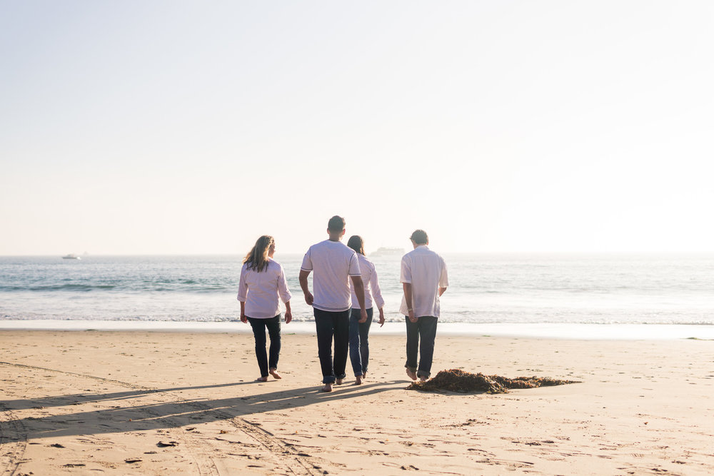 professional Family portraits Are family walking on the beach of family walking on beach being backlit during Golden hour at Crystal Cove State Beach in Newport