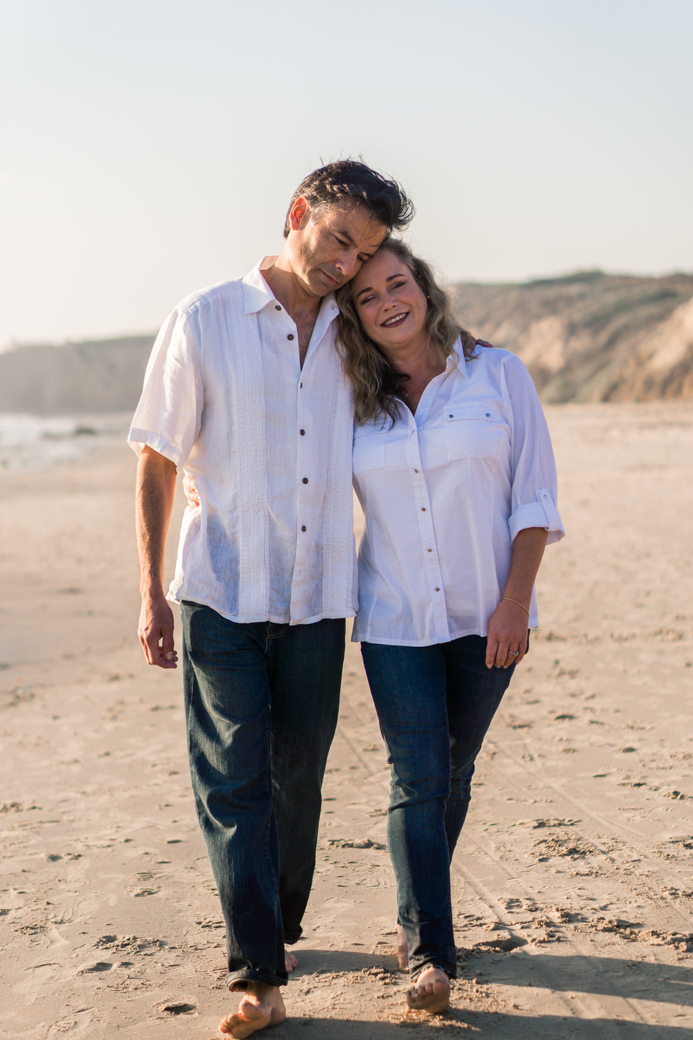 Family portraits of husband and wife walking on the beach holding hands and hugging at Crystal Cove Beach at Crystal Cove Beach in Newport during Golden hour