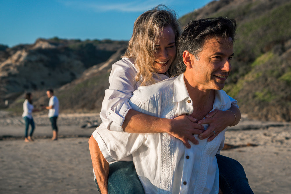 Family portraits of husband and wife walking on the beach having fun Crystal Cove Beach at Crystal Cove Beach in Newport during Golden hour