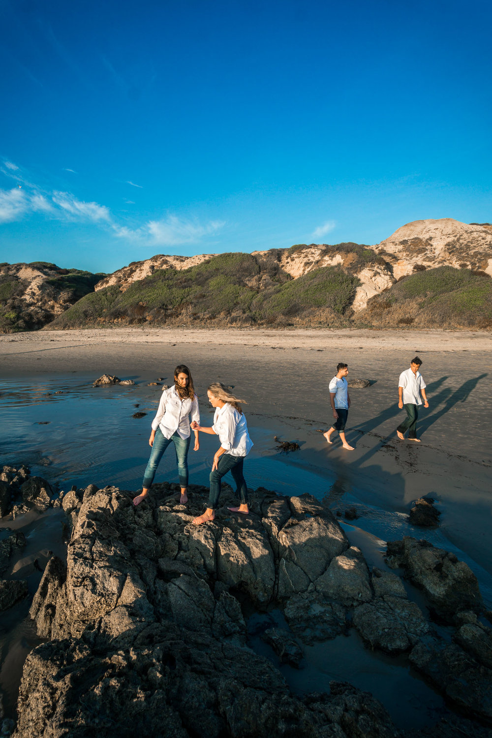 Family portraits of family beach combing on rocks and tidepools during Golden hour at Crystal Cove State Beach in Newport