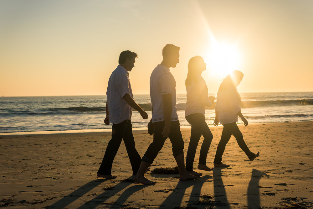 Family portraits of family silhouette walking on the beach during Golden hour at Crystal Cove State Beach in Newport