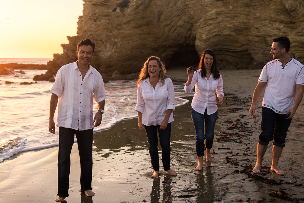 Family portraits of family walking on the beach laughing during Golden hour at Crystal Cove State Beach in Newport