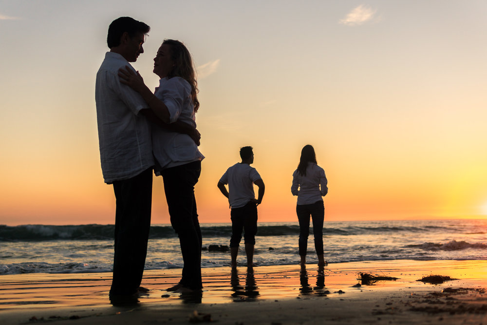 Family portraits of family silhouettes with a  glassy seashore while enjoying the sunset together during Golden hour at Crystal Cove State Beach in Newport