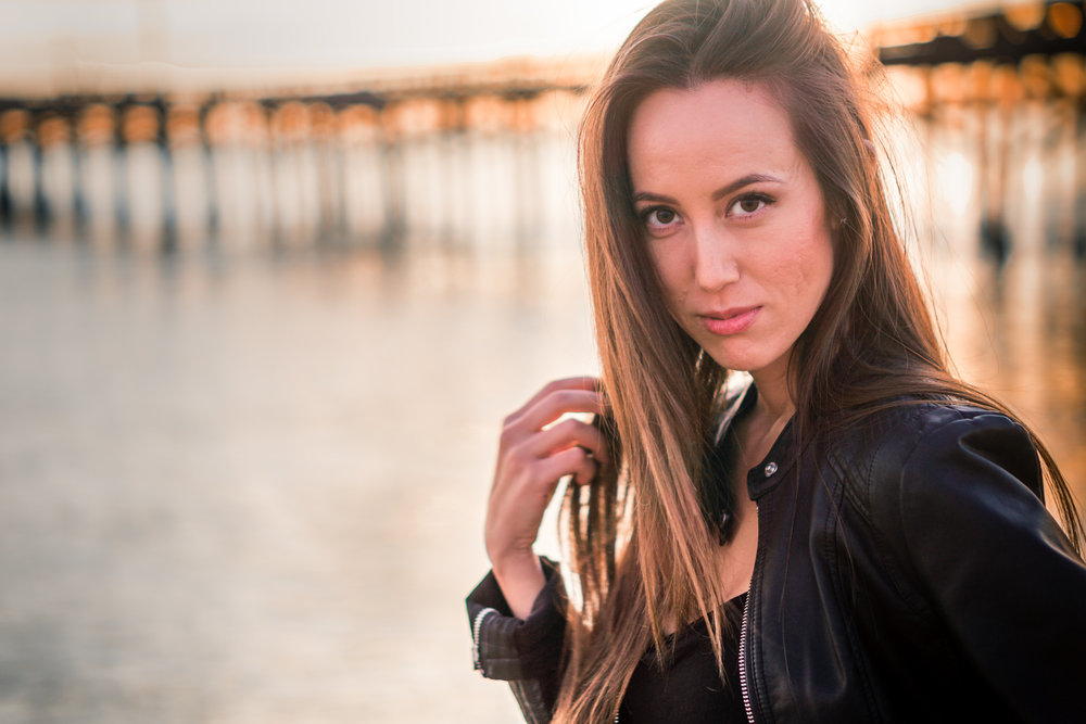 Natural light Fashion Portrait of female model wearing black leather jacket and blue jeans taken during Golden hour At Balboa Pier in Newport Beach