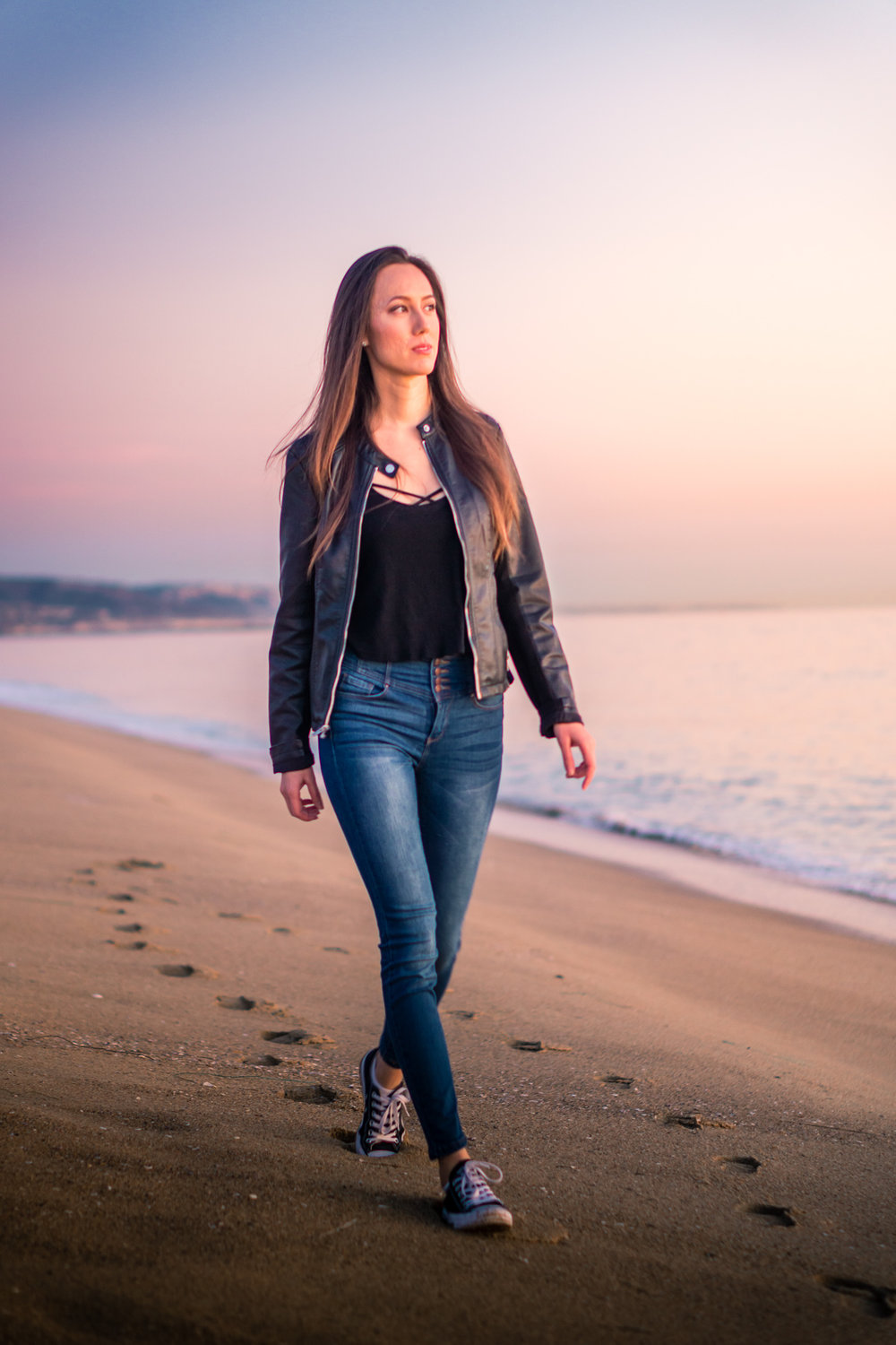 vibrant Natural light Fashion Portrait of woman wearing black leather jacket and blue jeans walking on beach during Golden hour At Balboa Pier in Orange County