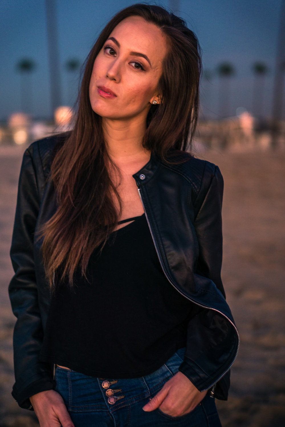 vibrant Natural light Fashion Portrait of woman posing in black leather jacket and blue jeans walking on beach during Golden hour At Balboa Pier in Newport Beach