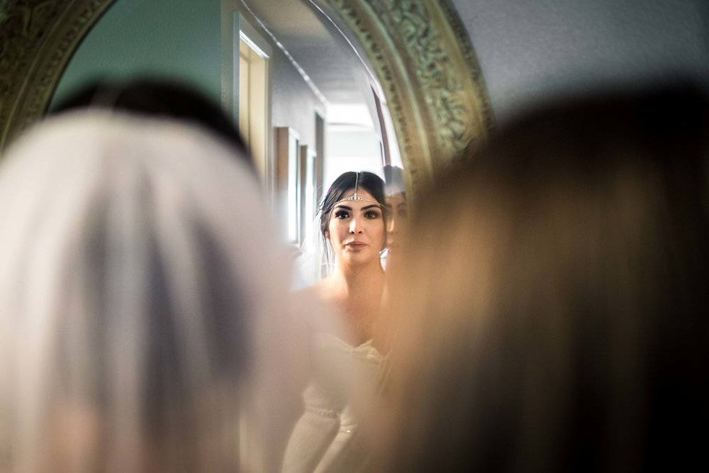 Candid wedding Photo taken of the bride with her mother looking in the mirror while she's getting ready before her wedding on Balboa Island