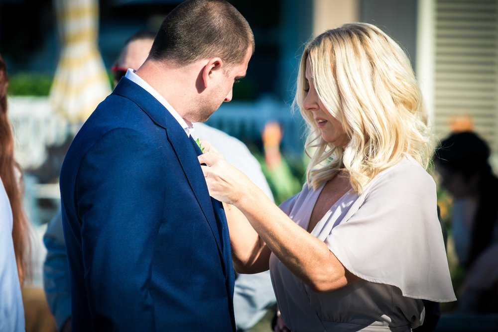 The groom's mother helping him pin on his boutonniere   before his wedding ceremony on Balboa Island