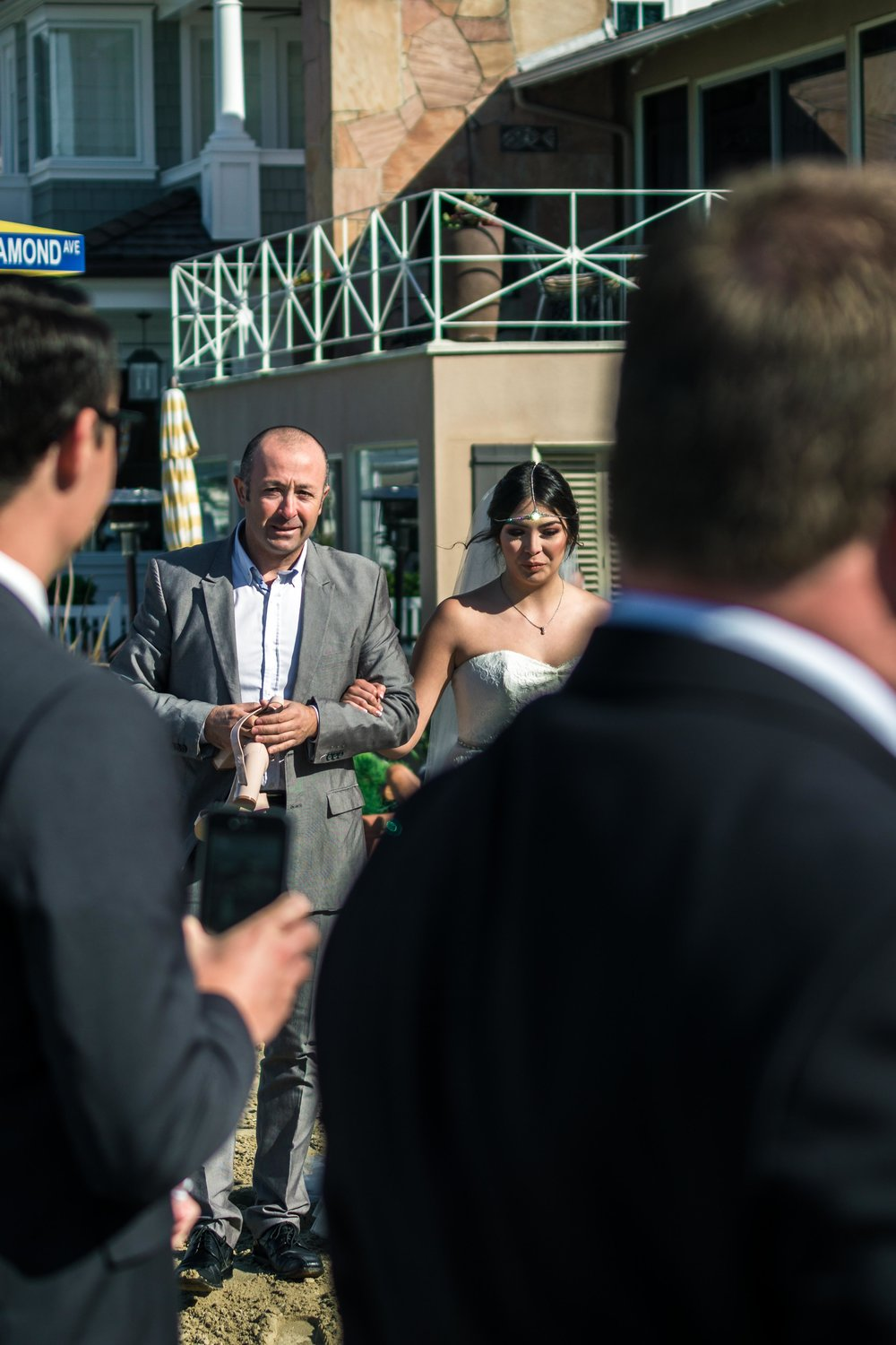 The brides father walking her down the aisle during her ceremony on Balboa Island