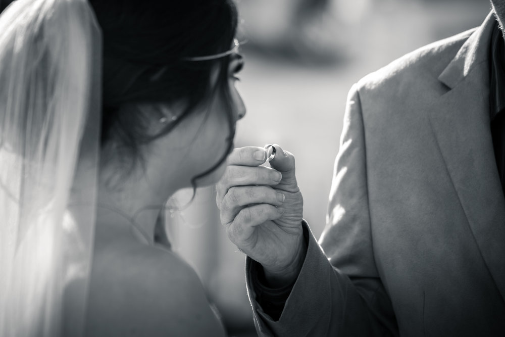 Black-and-white photo  of The pastor handing the wedding ring to The bride at the altar