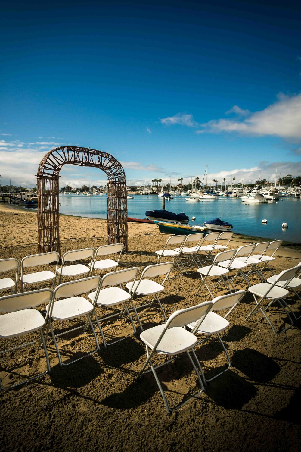 The wedding ceremony before the guests arrive on the beach on diamond street on Balboa Island Newport Beach