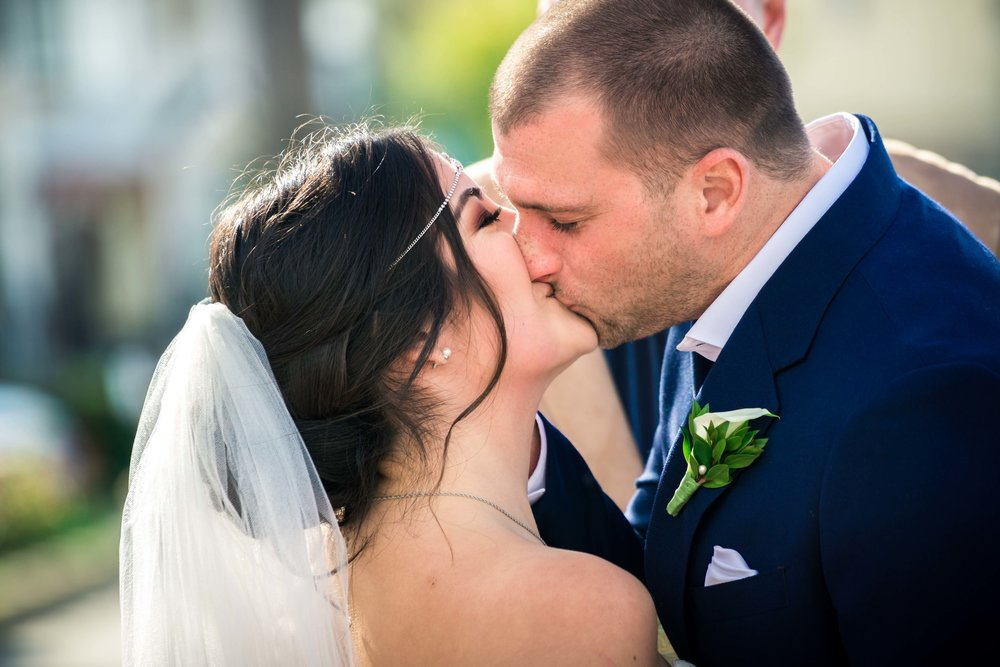 The bride and groom kissing at the altar During their ceremony
