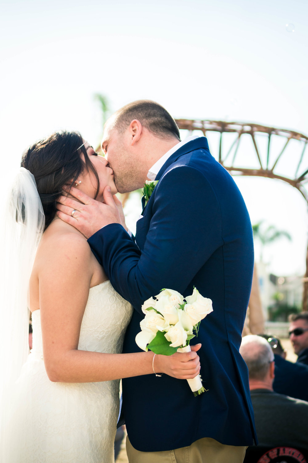 The groom passionately kissing his bride after they have been married