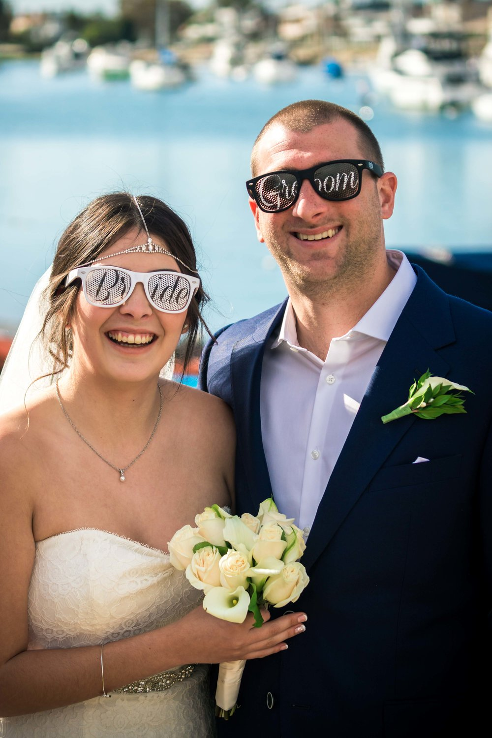 Bride and groom smiling and wearing their cool sunglasses