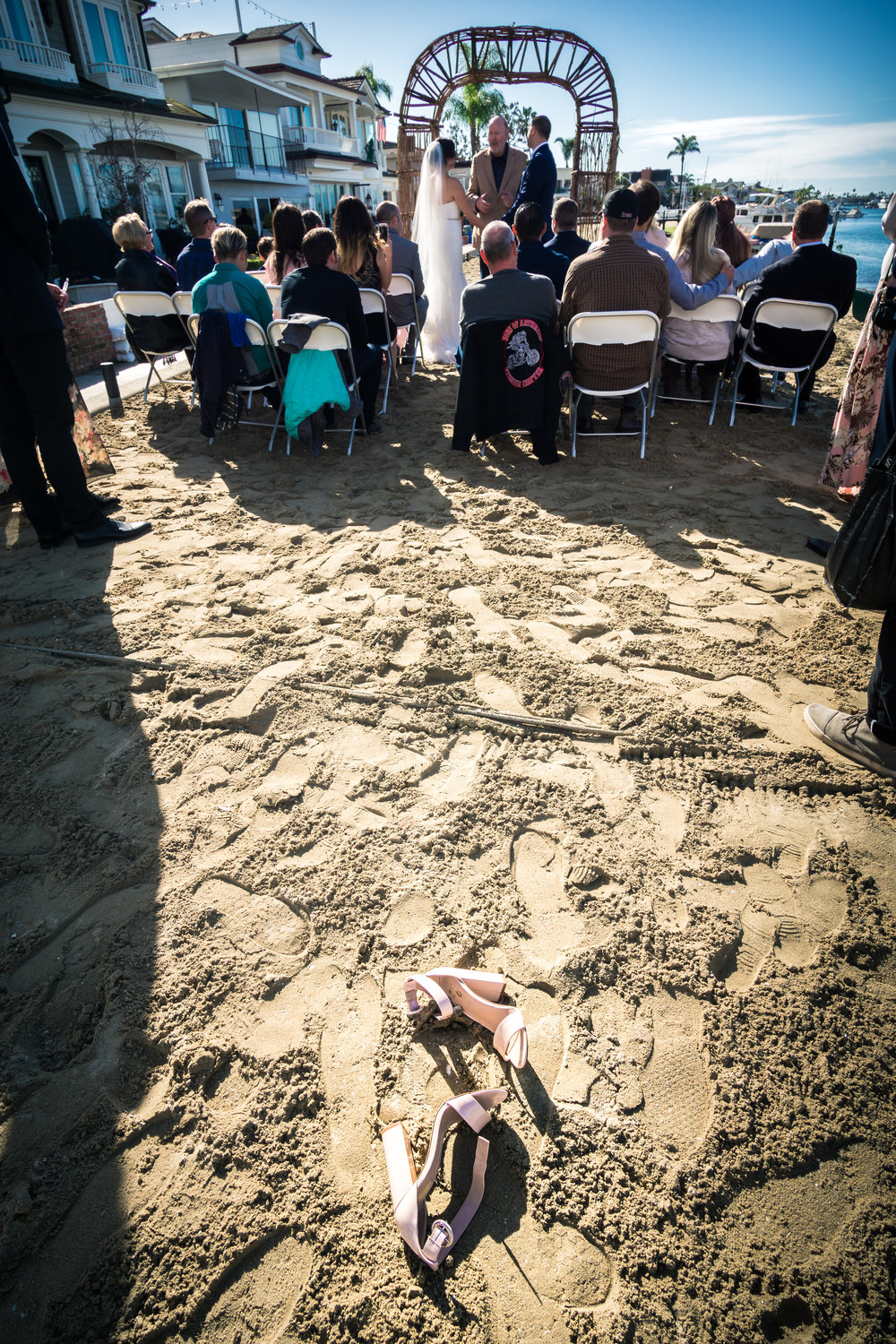 The bride shoes in the sand on the beach during the wedding ceremony on Balboa Island