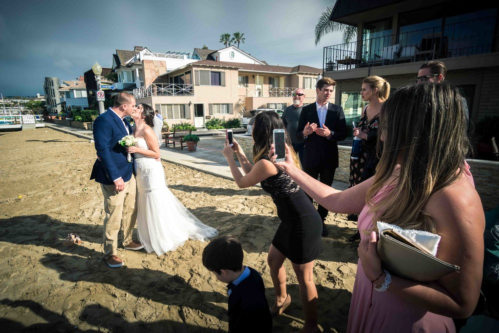 Wedding guests taking photos of bride and groom kissing