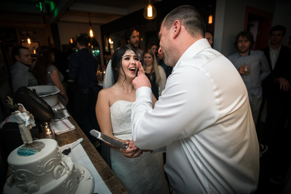 The groom smearing wedding cake on the brides face