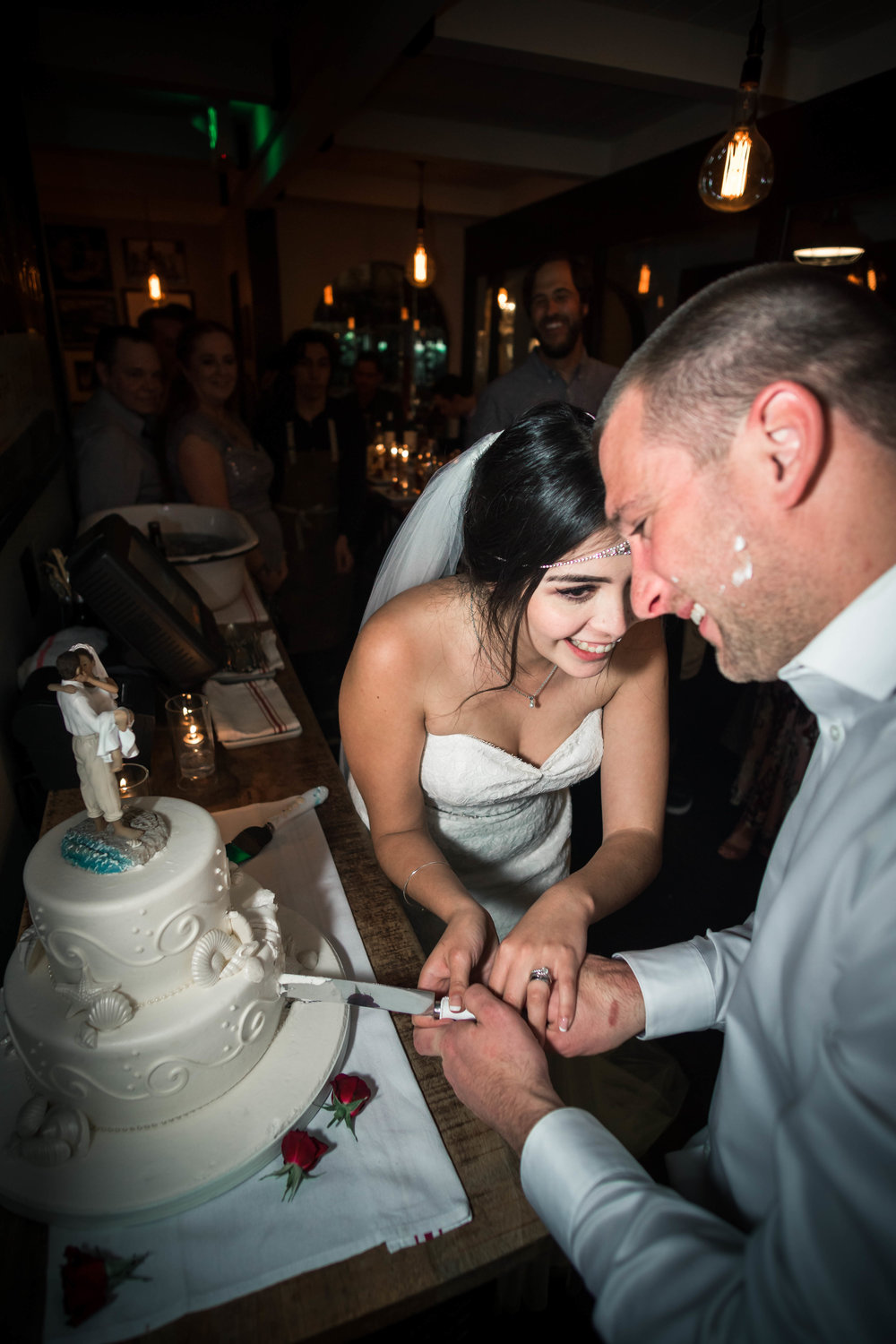Bride and groom cutting The wedding cake And laughing