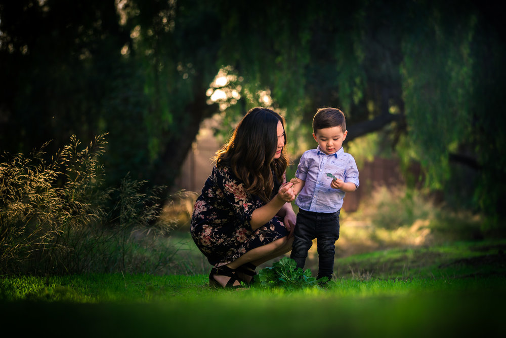 Candid photo of a little boy and mother during a Family portrait photo shoot in Fullerton on the Juanita Cooke greenbelt and Trail with vibrant green trees and grass and the golden hour sun