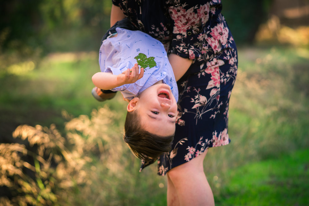 Candid photo of a little boy laughing with mother during a Family portrait photo shoot in orange county on the Juanita Cooke Trail with vibrant green trees and grass and the golden hour sun