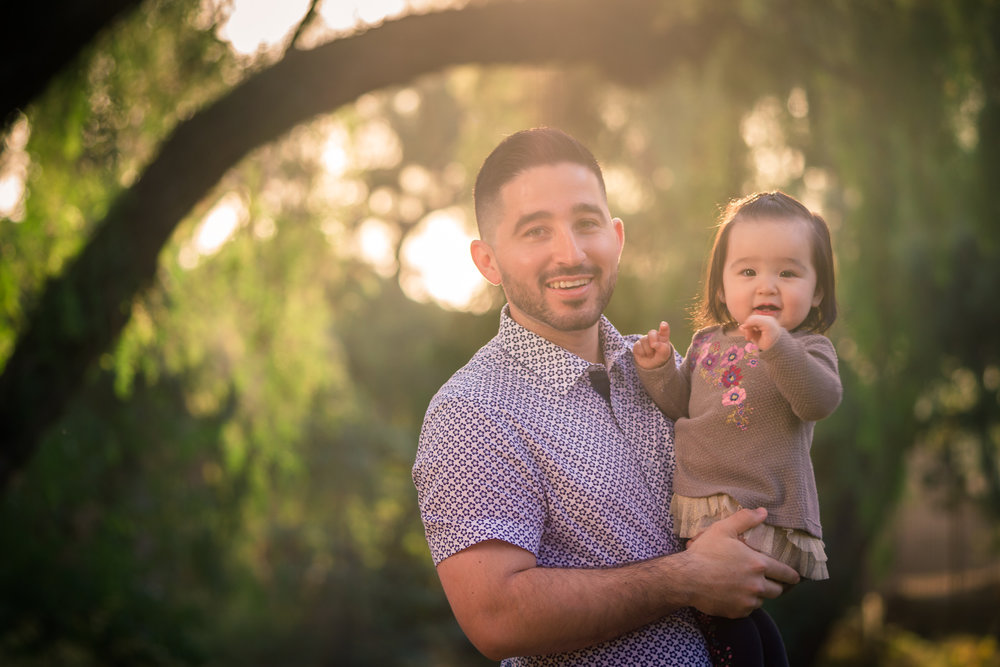 Candid photo of a little girl smiling with father during a Family portrait photo shoot in orange county on the Juanita CookeTrail with vibrant green trees and grass and the golden hour sun