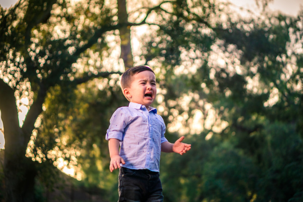 Portrait of a cute little boycrying during a family portrait session in fullerton orange county taken by joseph barber photography
