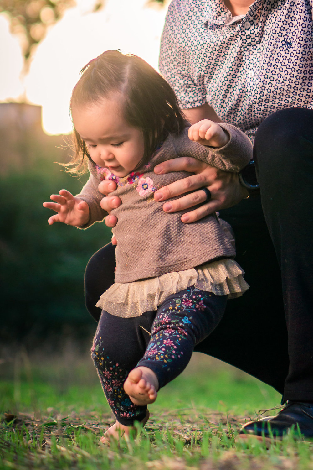 Portrait of a cute Little baby girl learning to walkin the grass on the Juanita Cooke Trail in Fullerton during a family portrait session