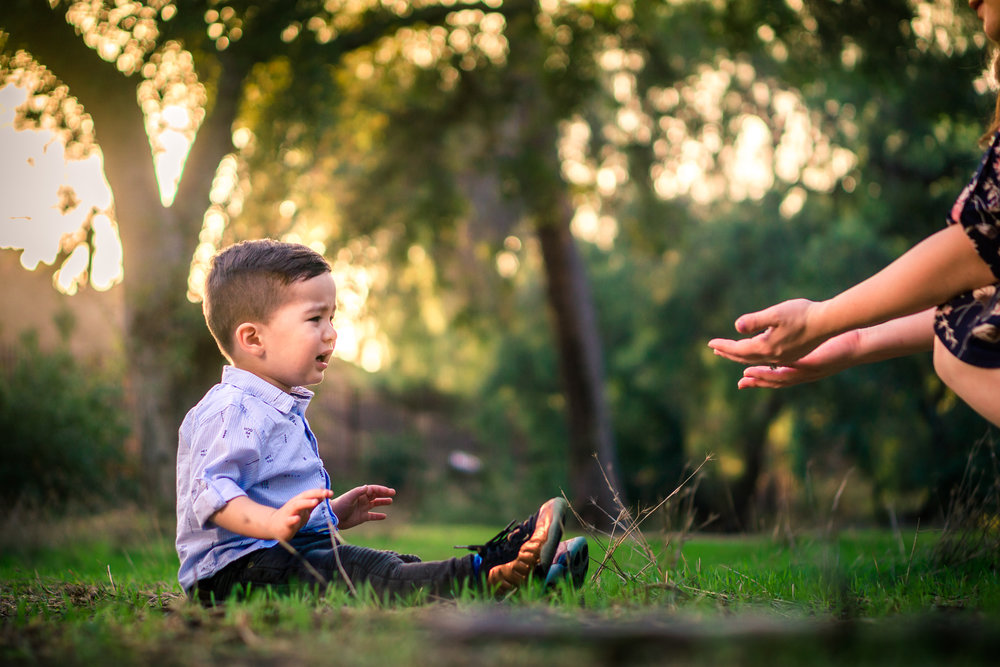 Portrait of a cute little boy crying with mother helping him during a family portrait session in fullerton orange county taken by joseph barber photography