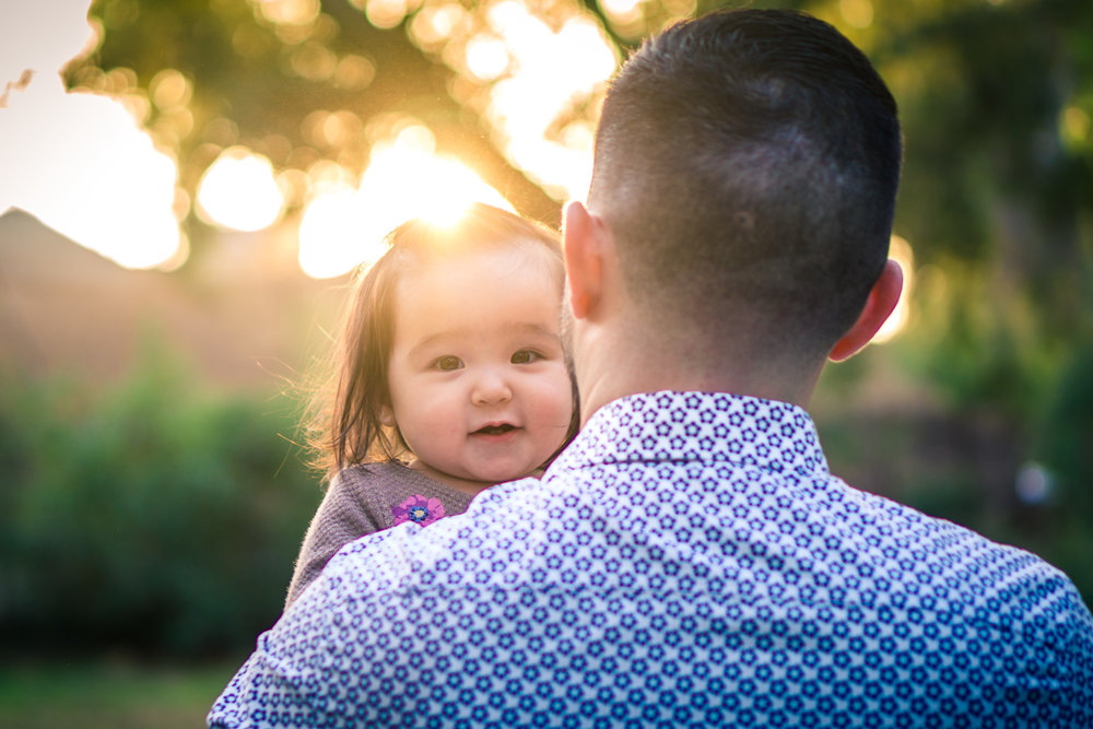 Portrait of a cute little baby girl looking back on her fathers shoulders during a family portrait session in fullerton orange county taken by joseph barber photography