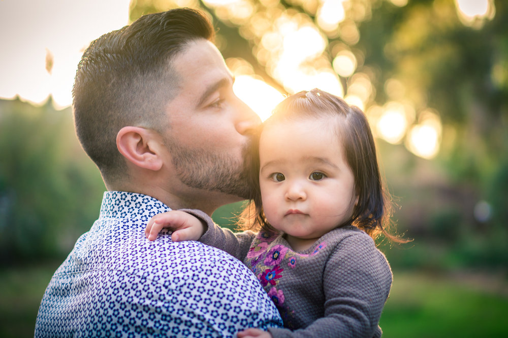 Portrait of a father kissing hiscute little baby girlduring a family portrait session in fullerton orange county taken by joseph barber photography