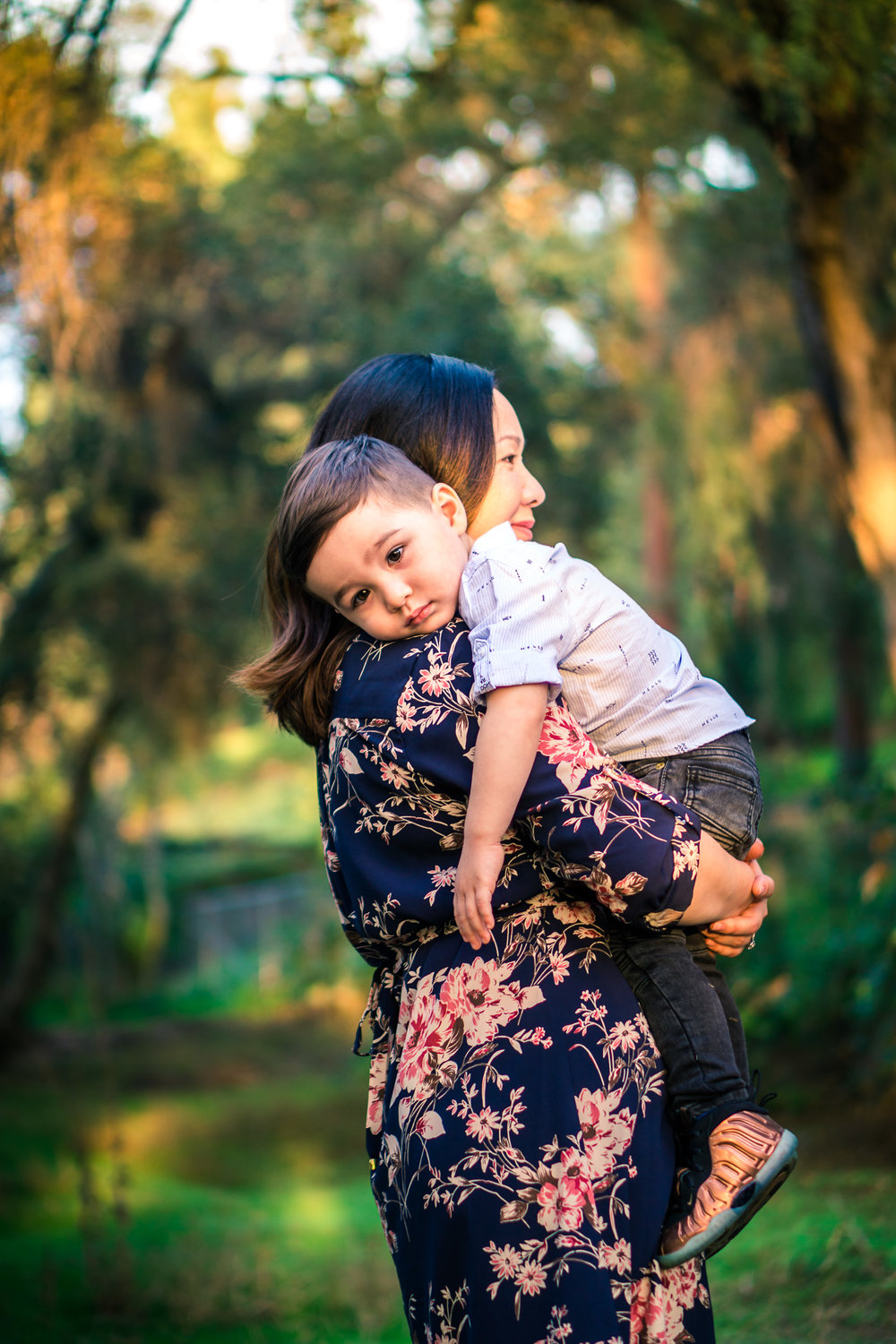 candid photo of a mother holding tired little boy on his shoulder during a family portrait session on the juanita cooke trail in fullerton orange county taken by joseph barber photography