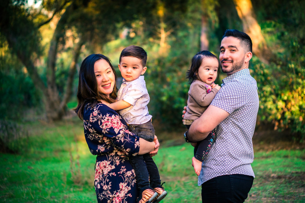 photo of a mother and father holding their little children during a family portrait session  on the juanita cooke trail in fullerton orange county taken by joseph barber photography