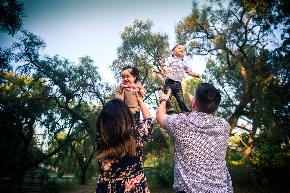 photo of a mother and father tossing up their little children during a family portrait session  on the juanita cooke trail in fullerton orange county taken by joseph barber photography